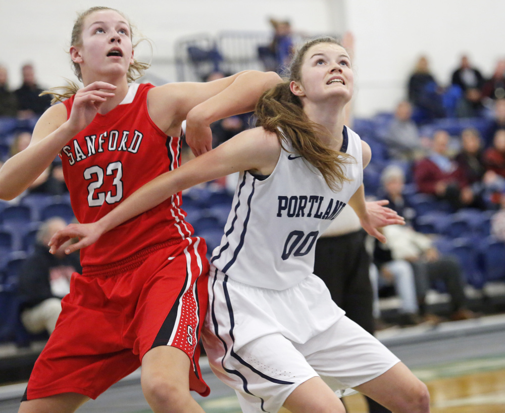 Rose Griffin of Portland boxes out Sanford freshman Paige Cote while preparing to pull down a rebound Tuesday during Sanford's 50-37 victory at the Portland Expo. Cote finished with 15 points and 10 rebounds.
