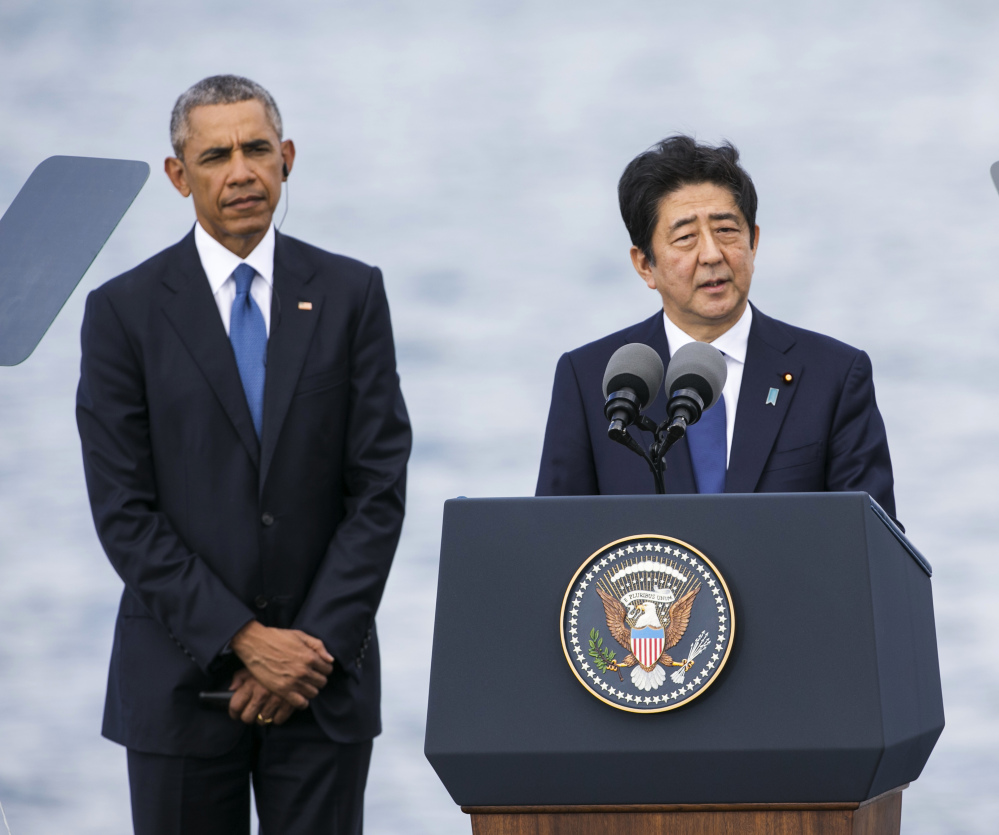 Japanese Prime Minister Shinzo Abe appears with U.S. President Obama at Joint Base Pearl Harbor Hickam on Tuesday in Honolulu. Abe and Obama made a historic pilgrimage Tuesday to the site where the devastating surprise attack sent America marching into World War II.