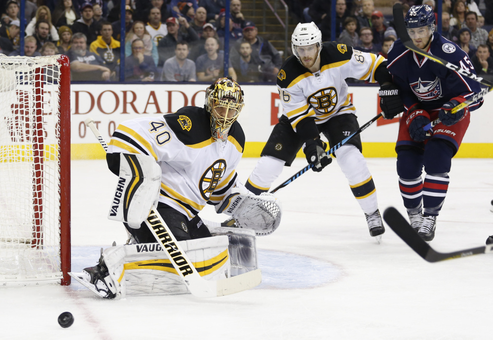 Bruins goalie Tuukka Rask makes a save as teammate Kevan Miller and the Blue Jackets' Lukas Sedlak look for the rebound during the second period of Tuesday night's game in Columbus, Ohio.