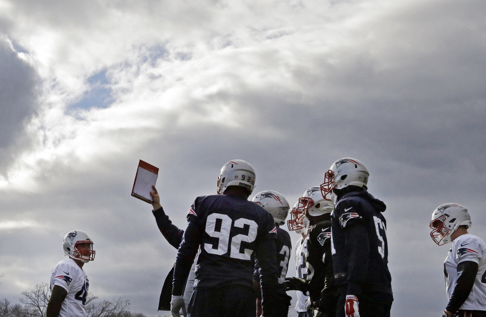 New England Patriots defensive players huddle to look at a playbook during practice Wednesday in Foxborough, Mass. The Patriots boast one of the best defenses in the National Football League this season.