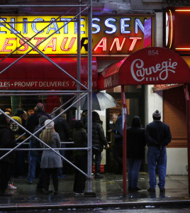 People wait in line to eat at the Carnegie Deli in New York on Thursday. After 79 years of serving up heaps of cured meat, the Carnegie shut down for the last time Friday.