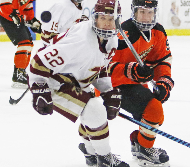 Chase Wescott, left, of Thornton Academy and Tyler Laflamme of Biddeford keep their eye on the puck during a Class A South hockey game Saturday at Biddeford Ice Arena. Biddeford won, 3-0.