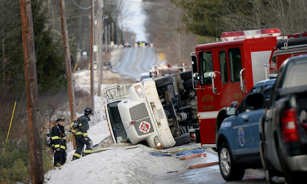 A truck lies on its side at the scene of an oil spill on Route 22 in Buxton on Tuesday.