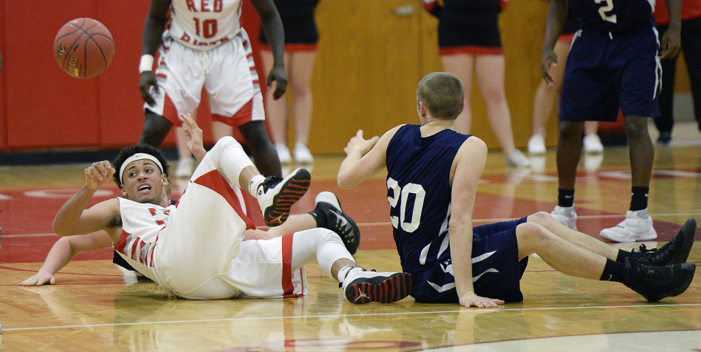 South Portland's Ansel Stilley passes the ball from the ground as Portland's Griffin Foley plays defense in Friday night's boys' basketball opener.