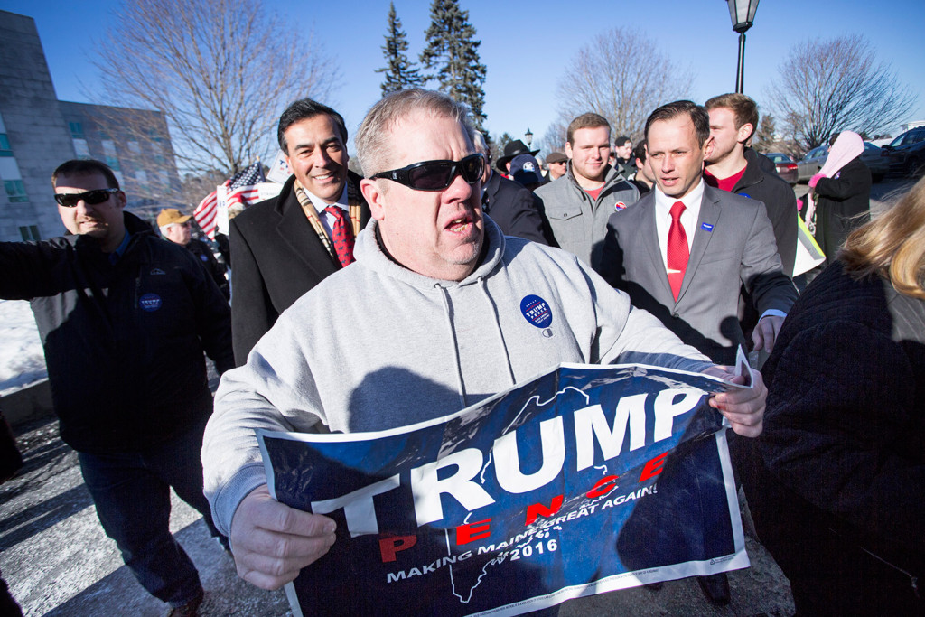 Trump supporters escort Maine Republican Party Chairman and elector Rick Bennett, second from left, into the State House in Augusta on Monday.