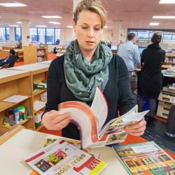 Sonya Durney, reference librarian for the Portland Public Library, flips through a copy of Library Journal to learn about newly published book titles.
