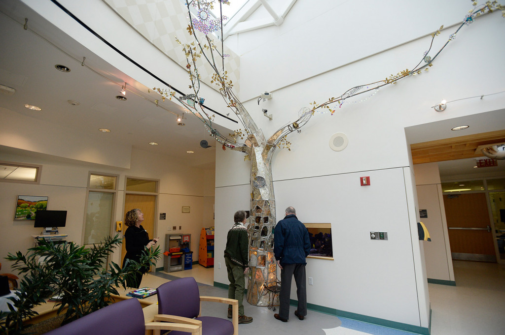 Visitors to the Barbara Bush Children's Hospital at Maine Medical Center in Portland on Wednesday look at the new stained glass tree created by Maine artist Laura Fuller.