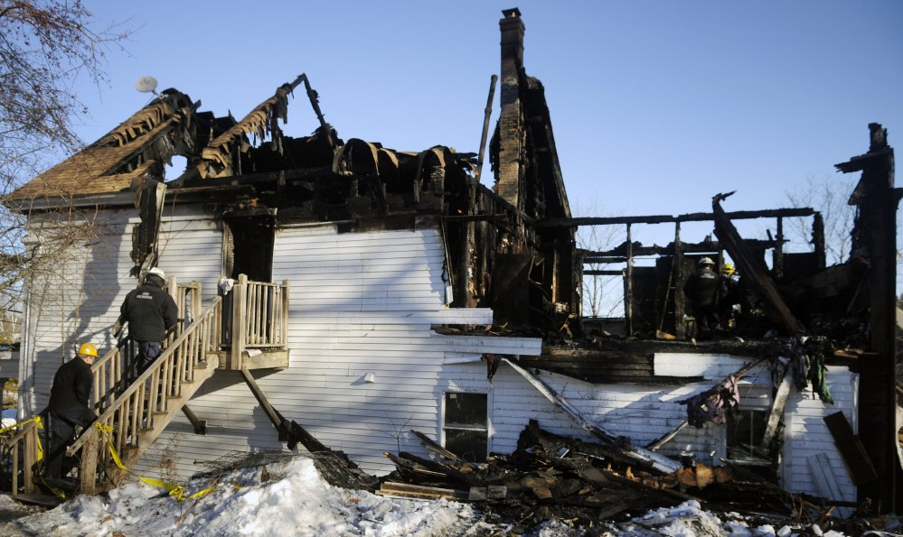 Investigators from the Fire Marshal's Office examine the ruins of a building that burned in Richmond on Sunday.