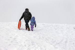 Max Mejia walks daughter Itzayana up the sledding hill at Eastern Prom after a final run for the day.