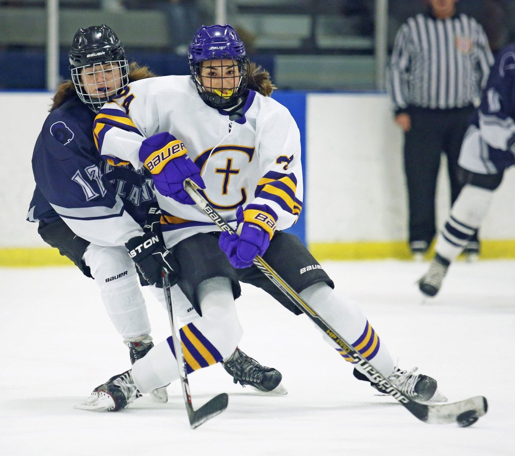 Abby Lamontagne of Cheverus shoots the puck as Maeve LeClair of Portland defends.