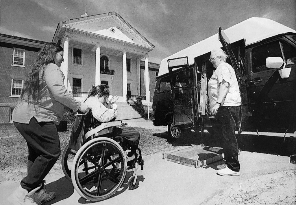 Mental health workers escort the last resident of Pineland Center to a van that would take her to a private home as the center closed its doors in 1996.
