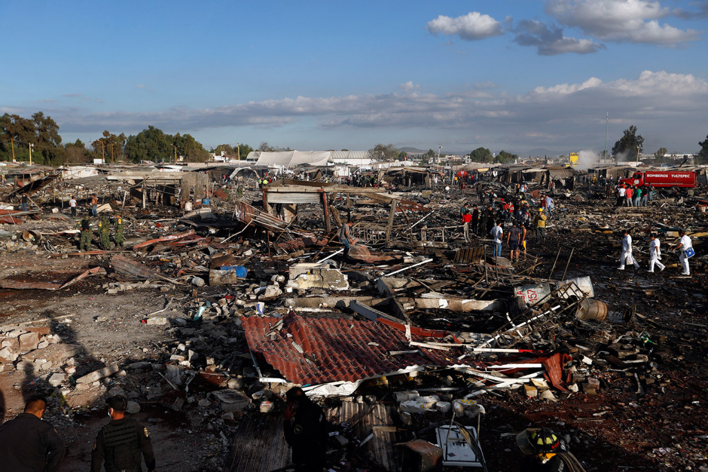 Firefighters and rescue workers walk through the scorched ground of the open-air San Pablito fireworks market outside Mexico City on Tuesday. Associated Press/Eduardo Verdugo