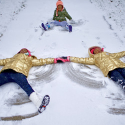 The Blue sisters – Sky, left, and Star – make side-by-side snow angels in Lincoln Park Monday afternoon while niece Lauryn Blue, top, learns how it's done.