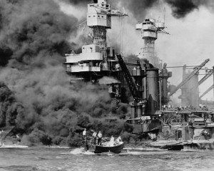 In this Dec. 7, 1941 photo, a small boat rescues a seaman from the USS West Virginia burning in the foreground in Pearl Harbor, Hawaii, after Japanese aircraft attacked the military installation. More than 2,300 U.S. service members and civilians were killed in the strike that brought the United States into World War II. U.S. Navy via AP