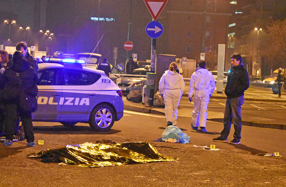 The body of Anis Amri, the suspect in the Berlin Christmas market truck attack, is seen covered with a thermal blanket next to Italian officers in a suburb of Milan Reuters