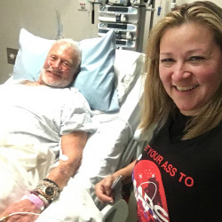 In this Friday, Dec. 2, 2016, photo provided by Christina Korp, right, Buzz Aldrin lies in a hospital bed in Christchurch, New Zealand. Aldrin, the second man to walk on the moon, was evacuated from the South Pole to New Zealand where he was hospitalized in stable condition. (Christina Korp via AP)