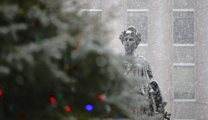Snow gathers on The Lady of Victory statue and Portland's Christmas tree in Monument Square.