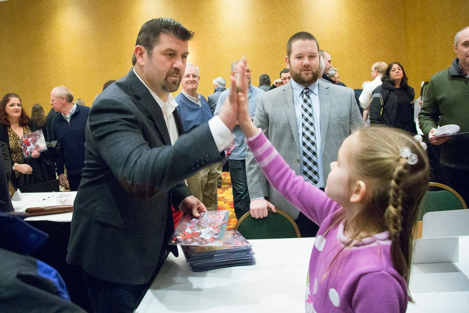 Jason Varitek, the catcher for Boston's 2004 and 2007 World Series championship teams, gives a high-five to Dominique Giroux-Pare, 8, of Winslow during the Portland Sea Dogs' annual Hot Stove Dinner on Friday night.