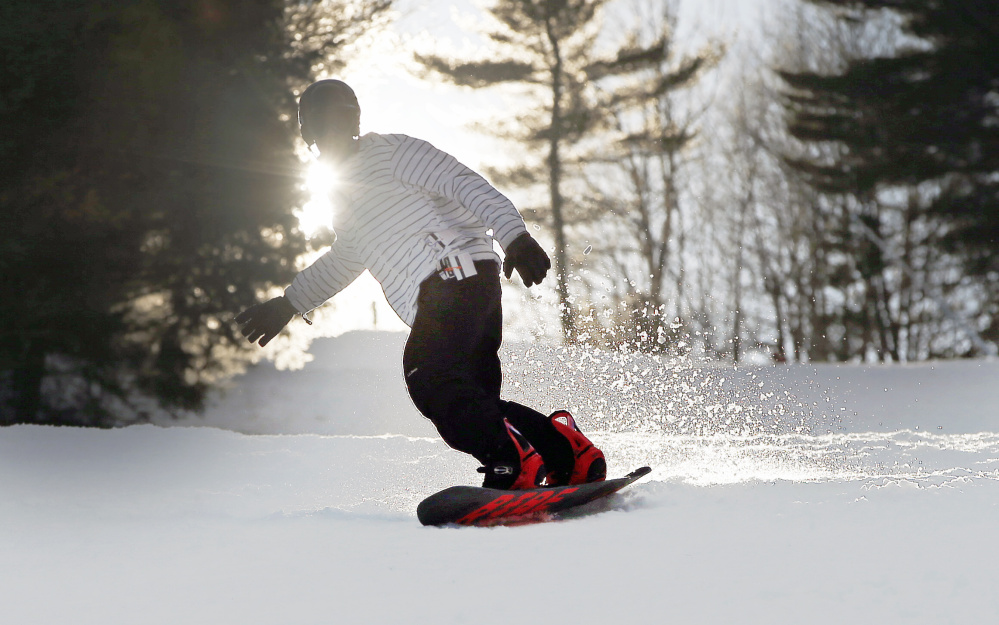 A snowboarder is silhouetted by the late-day sun last week at Shawnee Peak ski area in Bridgton. Maine's snow sports industry is hoping that this month's cold and snowy weather foreshadows the kind of old-fashioned winter that can help it forget the lackluster season last year. This December has been far  colder and snowier than last year, according to data from the National Weather Service in Gray. That bodes well for the state's ski industry, which employs thousands and generates an economic impact of about $300 million annually, according to the Ski Maine Association.