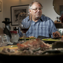 "Musician Denny Breau talks with guests eating a meal of pot roast with gravy and mashed potatoes he cooked at the home of Food Editor Peggy Grodinsky in Portland. Breau's song ""Pot Roast"" pays tribute to a dish that inspires happy memories for him."
