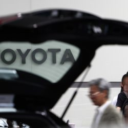 People look at a car on display at Toyota's Tokyo headquarters. President-elect Donald Trump has threatened Toyota for building its products in Mexico rather than the U.S.