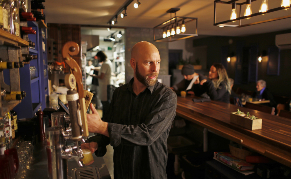 Keith Johnson, co-owner of Owl + Elm, pours a Banded Horn pilsner during a busy weeknight shift.
