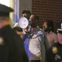 Mohamed Omar chants through a bullhorn while police monitor the scene on Commercial Street during a Black Lives Matter protest last July 15. Seventeen of the 150 protesters were arrested on misdemeanor charges, which could be dropped if a judge approves a deal calling for a mediated meeting where both police and the defendants get a chance to speak their piece.