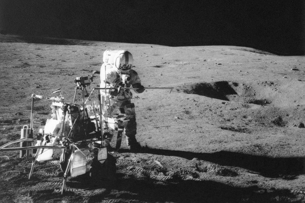 Apollo 14 astronaut Alan B. Shepard Jr. conducts an experiment near a lunar crater, using an instrument from a two-wheeled cart carrying various tools. Analysis of material collected on that trip has led a research team to conclude that the moon formed within 60 million years of the birth of the solar system.