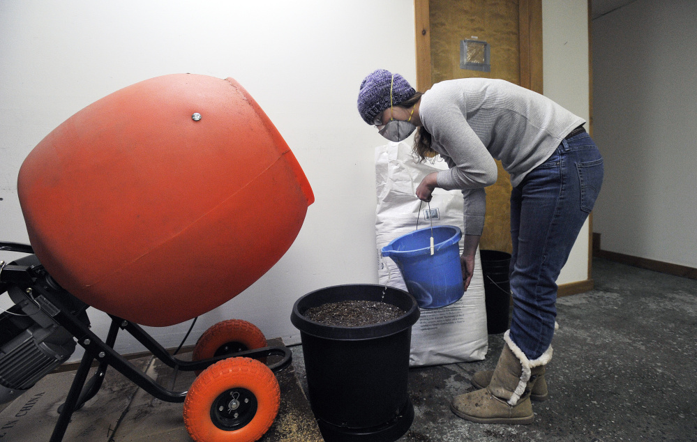 At East Coast CBDs in Unity, Billie Pirruccello adds water to soil she just mixed. East Coast CBDs also uses high-efficiency heat pumps and forgoes chemical fertilizers in an effort to boost sustainability.