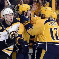Predators left wing Filip Forsberg, center, celebrates with center Mike Fisher (12) after Forsberg scored what proved to be the game winner late in the second period. Bruins defenseman Brandon Carlo skates by after the goal.
