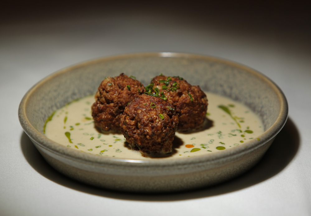Albondigas de cordero, a hot tapas plate of seared lamb meatballs served in oxtail jus and sherry cream at Toroso.