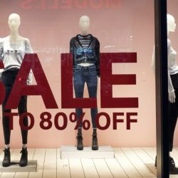 In this Wednesday, Jan. 11, 2017, photo, an H&M store window advertises a sale, in New York. On Friday, Jan. 13, 2017, the Commerce Department releases U.S. retail sales data for December. (AP Photo/Mark Lennihan)