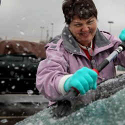 Mary Zinser scrapes a thick layer of ice off her windshield Friday in Arnold, Mo. A thick glaze of ice covered roads from Oklahoma to Illinois.