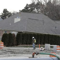 FILE - In this Jan. 4, 2017 file photo, a construction worker walks by a home collapsed by a sinkhole in Fraser, Mich.  Repairs to a broken sewer line that caused a massive sinkhole north of Detroit are estimated at more than $78 million.  (AP Photo/Carlos Osorio)