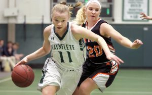 Lydia Giguere of Waynflete drives to the basket Tuesday while defended by Lindsay Tufts of North Yarmouth Academy during Waynflete's 45-40 victory at home.
