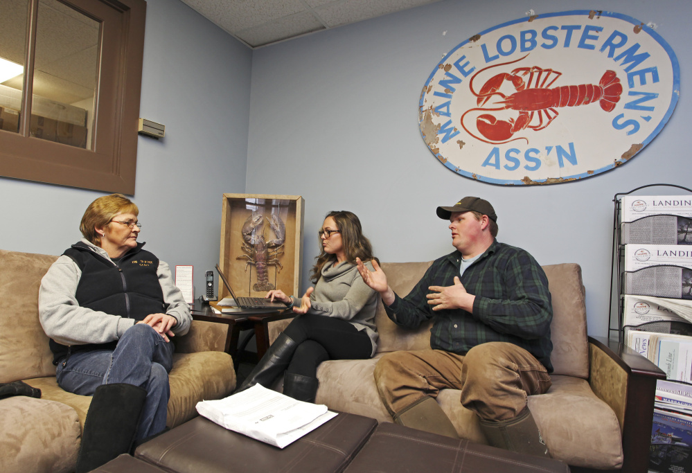 Alisha Keezer, center, a health insurance adviser, helps Cindy Welch sign up for coverage, joined by her lobsterman son, Chris Welch, at Maine Lobstermen's Association headquarters.