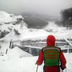 A rescuer stands in front of the Rigopiano Hotel, which was hit by an avalanche sometime Wednesday, in Farindola, Italy, early Thursday. Rescue workers were met with an eerie silence Thursday when they reached the four-star spa hotel.