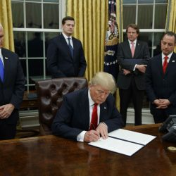 President Trump, flanked by Vice President Mike Pence, left, and Chief of Staff Reince Priebus, signs an order easing rules governing the Affordable Care Act Friday in the Oval Office.