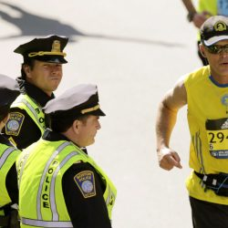 "Actor Mark Wahlberg, center left, dressed as a Boston Police officer, watches runners cross the finish line as he films a scene for his ""Patriot's Day"" movie at the 120th Boston Marathon in Boston. ""This was Boston's story,"" a spokeswoman said."