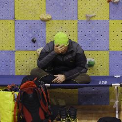 """A rescuer rests in a sports palace turned into a coordination center, in Penne, central Italy, early Saturday. An official said 23 were still missing but called that number """"provisional."""""""