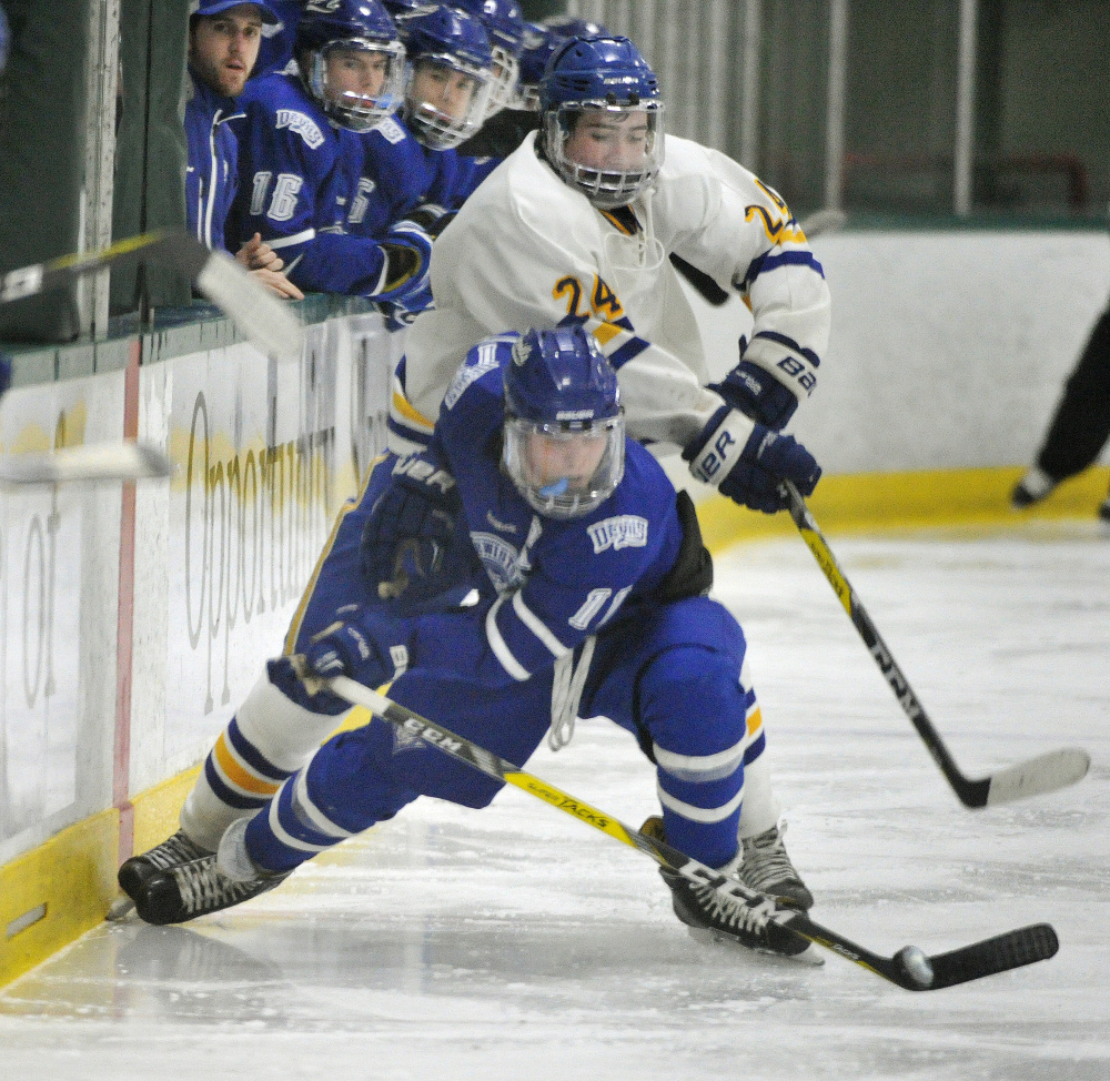 Lewiston's Jeremy Rancourt wins a race to the puck ahead of Falmouth's Alex Grade during their Class A hockey game Saturday at Family Ice Center. Rancourt finished with a goal and two assists, and Lewiston won, 5-4.