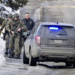 Police carrying weapons work on Saturday to convince an armed man to come out of an apartment on Front Place in Waterville.