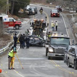 Police look over a car that was removed from the Stroudwater River along Spring Street in Westbrook on Sunday after it went over the guardrail, killing a man.