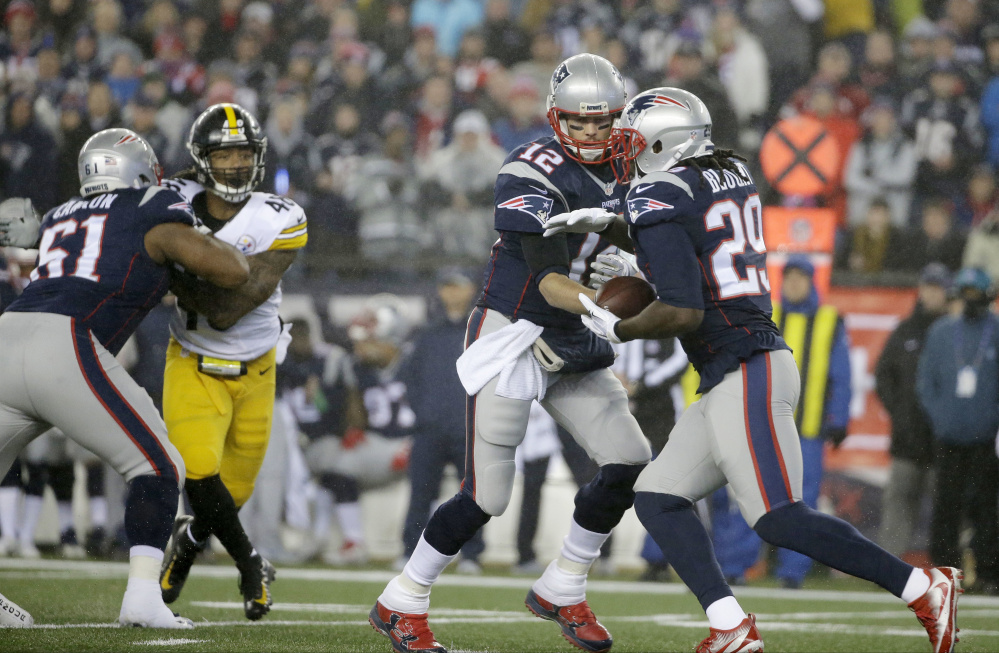 Patriots quarterback Tom Brady hands the ball to running back LeGarrette Blount during the first half.