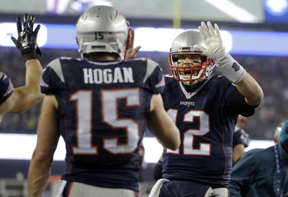 Patriots quarterback Tom Brady celebrates with wide receiver Chris Hogan after a touchdown pass during the first half .