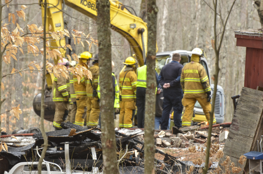 Firefighters from Washington and Liberty survey the damage Monday at the fatal fire on Cattle Pond Road in Washington.