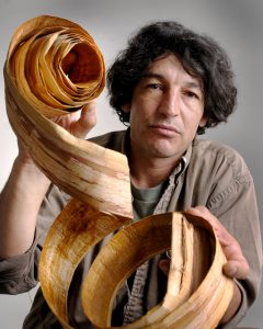 David Moses Bridges, a Native American builder of birch bark canoes, holds a piece of the cedar bark used in the making of his traditional canoes.