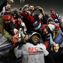 New England Patriots running back LeGarrette Blount holds the AFC championship trophy surrounded by fans after the AFC championship NFL football game Sunday in Foxborough, Mass. The Patriots defeated the the Pittsburgh Steelers 36-17 to advance to the Super Bowl.