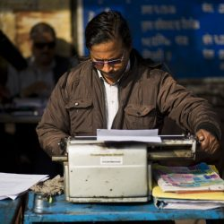 A roadside professional typist works near the stock exchange market in New Delhi, India. India still has a few thousand remaining professional typists, but even here, one of the last places in the world where the typewriter remains a part of everyday life, the end is coming.