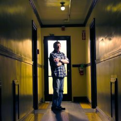 "Jenson Steel, a longtime HIV patient at the India Street clinic who helped others transition to a new health care provider, stands in the corridor outside his West End apartment. The directed transfer of patients to a new facility caused ""emotional trauma,"" said Steel, 67."